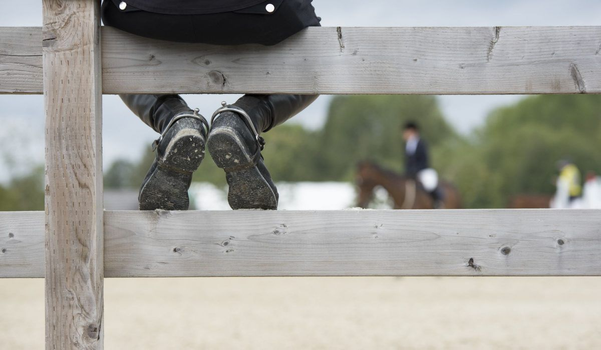 A coach since on a fence helping is student warm-up